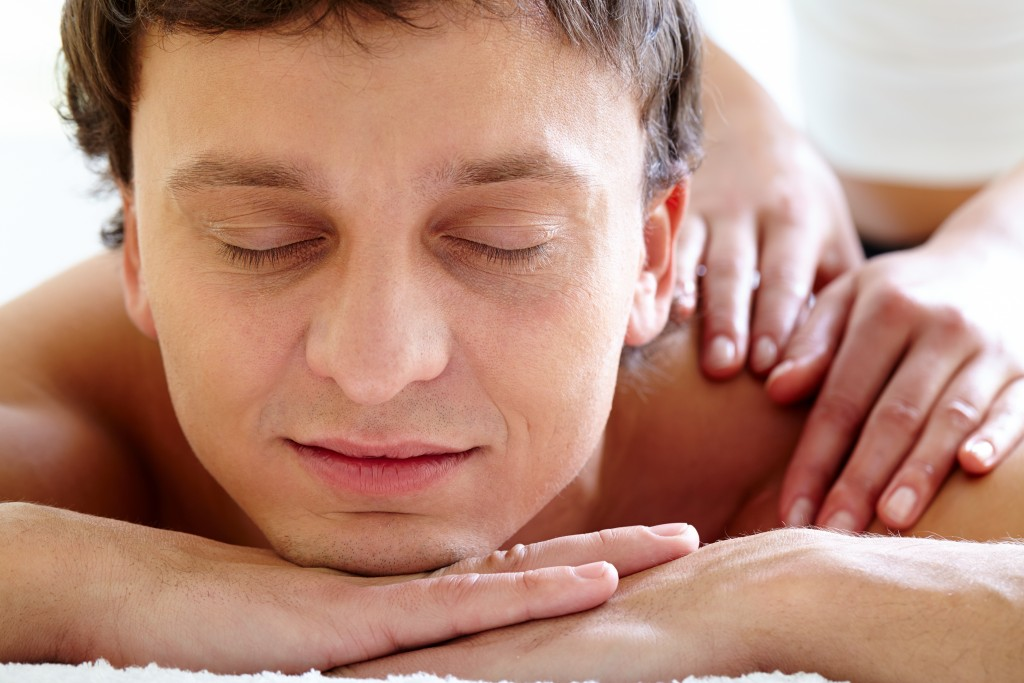 Portrait of young man enjoying the procedure of massage